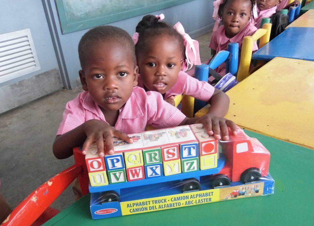 deti s nerozbalenou hračkou auta s kockami