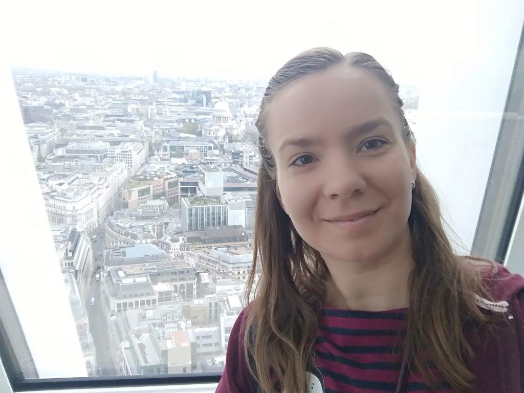 dievča s dlhými vlasmi v pásikavom tričku pred oknom za ktorým je vidieť veľkomesto