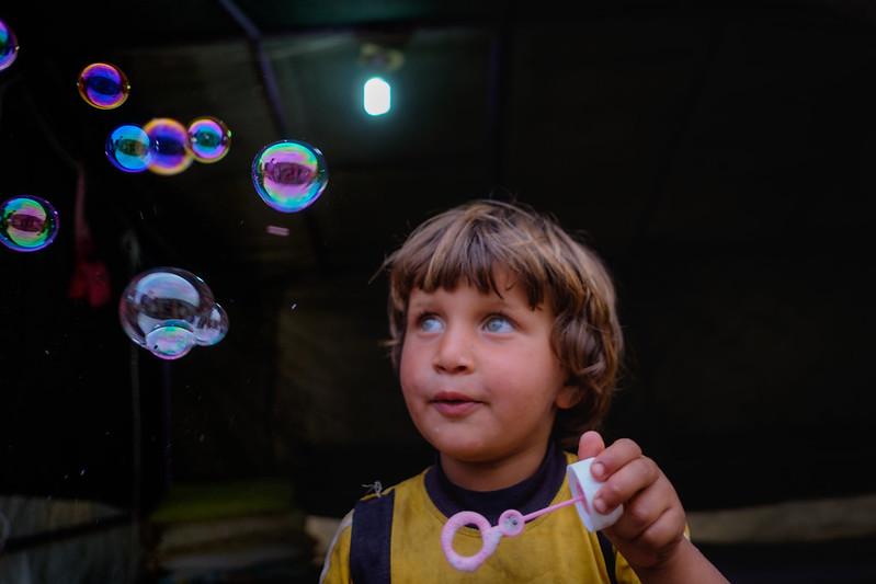 chlapec sa pozerá na bubliny z bublifuku