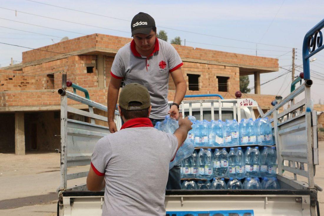 dvaja muži vykladajú fľaše vody z auta