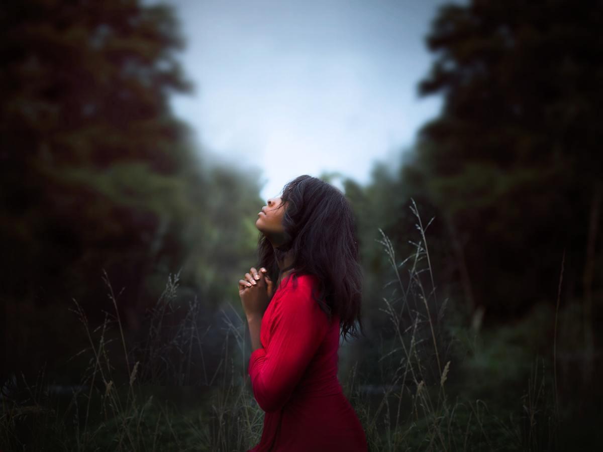 žena so spojenými rukami v lese