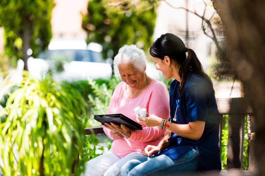 seniorka a opatrovateľka sedia v parku na lavičke