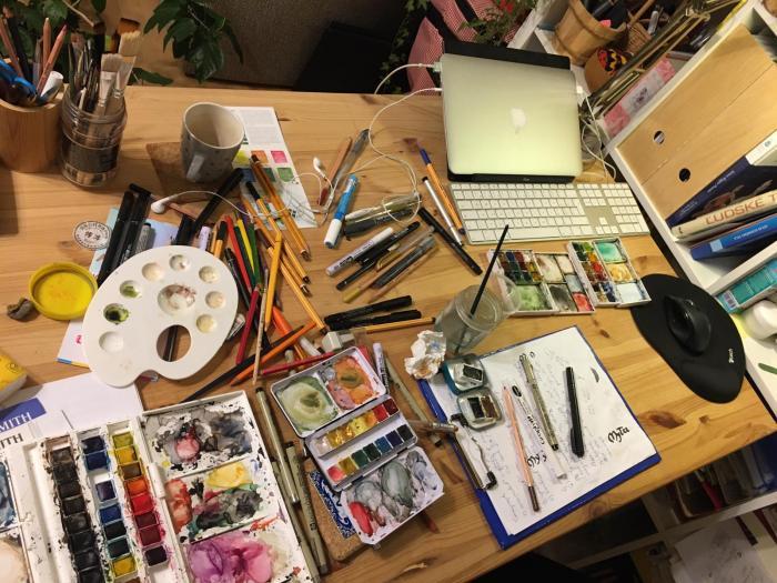 stôl plný pomôcok na maľovanie