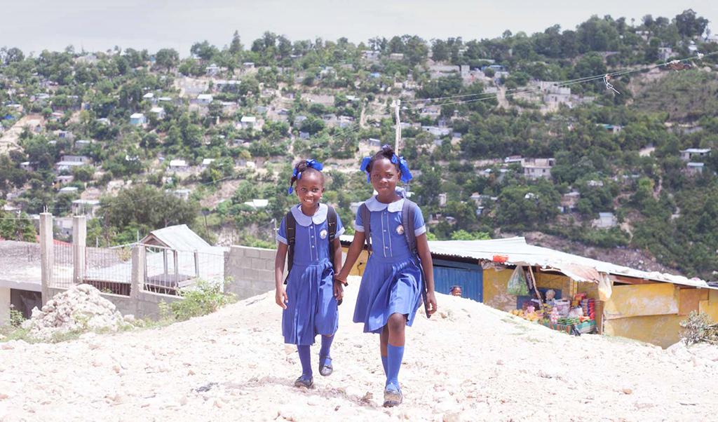 dve školáčky kráčajú s krajinou v pozadí