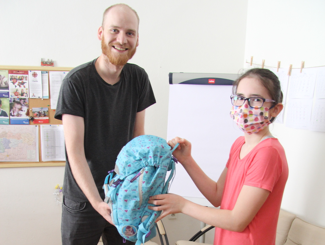 muž daruje školskú tašku dievčaťu