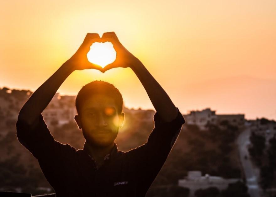 muž symbolizuje rukami srdce pri západe slnka
