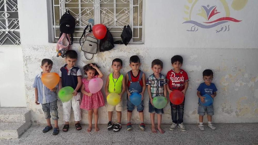 deti s balónmi stoja v zástupe pred budovou