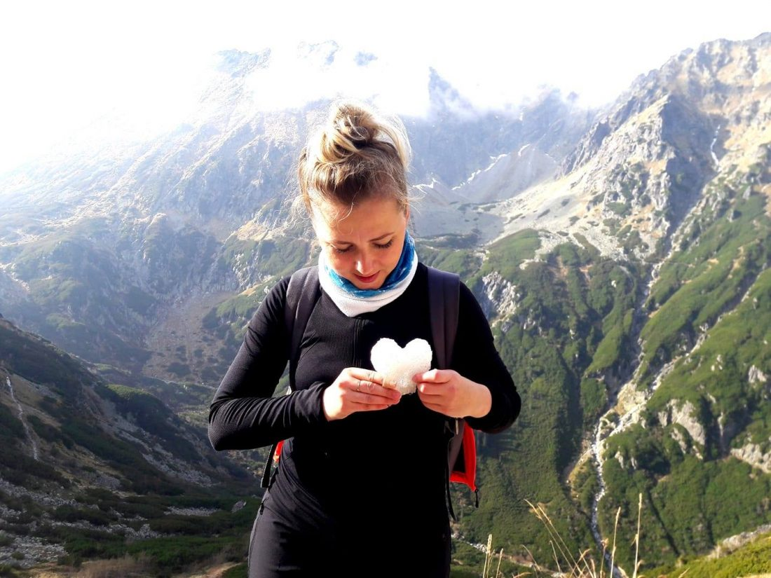 žena s vyrezaným srdcom z papiera s pohorím v pozadí