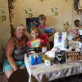 rodina za plným stolom darovaných potravín. Aj tak žijú rodiny na východe Ukrajiny.