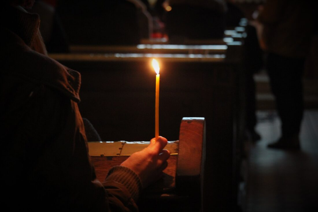 horiaca sviečka v šere kostola pri spoločnej modlitbe